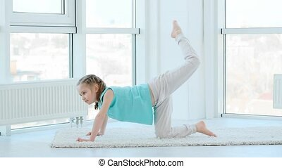 Cute little girl working out on floor at home