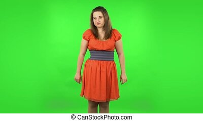 Cute girl worrying in expectation then frustration. Chubby girl in a coral dress with straight hair medium length and light eyes on green screen at studio