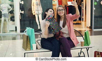 Cute girls are taking selfie in shopping mall posing with...