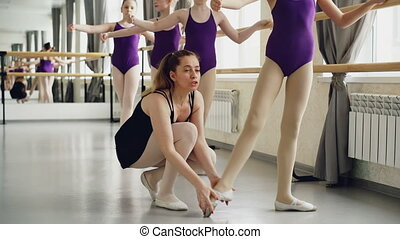 Cute girls diligent students of ballet school are stretching...