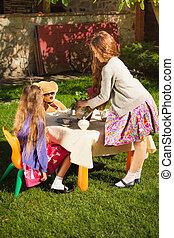 cute girls having tea party at yard