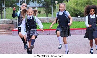 cute girls in uniform run along school yard against flowers...