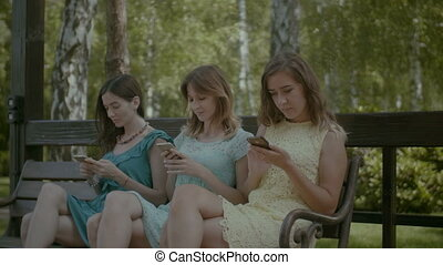 Cute girls networking with cellphone in park - Three pretty...