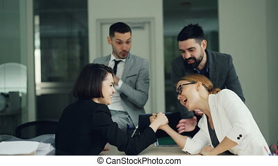Cute girls office workers are competing in arm wrestling...