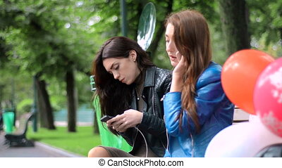 cute girls sitting on a bench in the park with mobile phones...