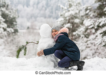 Cute girly with snowman in winter snowy Park.