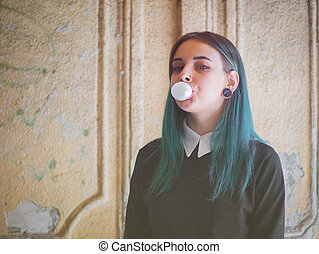 Cute gothic model blows bubblegum. Street punk or hipster...