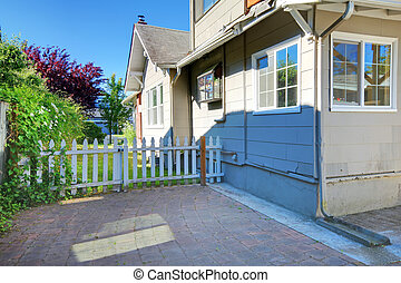 Cute grey house exterior with patio and small fence