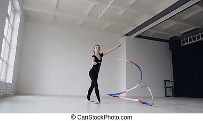 Cute gymnastics in black body performs the gymnastics exercise with a colored ribbon in the white studio. Cute girl makes stretching exercise in gymnastic school