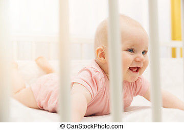 cute happy baby girl playing in crib