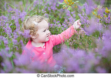 Cute happy baby girl playing with beautiful purple flowers in a