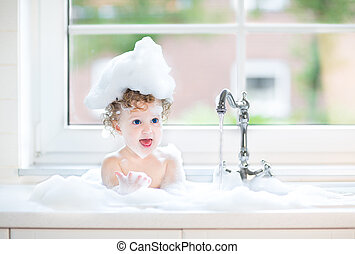 Cute happy baby girl with big blue eyes playing with water in a