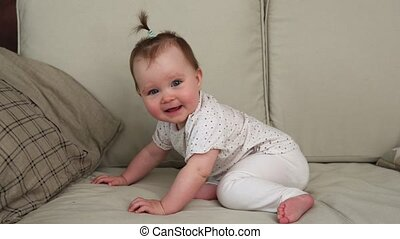 Cute happy baby smiling on a sofa