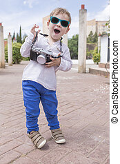Cute happy boy with vintage photo camera like little tourist
