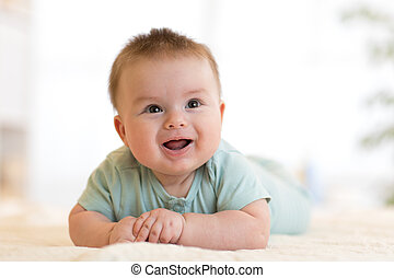 cute happy caucasian baby boy lies smiling on bed