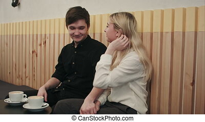 Cute happy couple enjoying a cup of coffee while on a date at a cafe