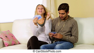 Cute happy couple playing cards