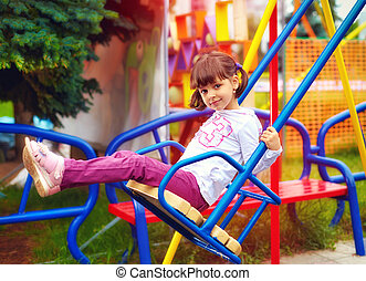 cute happy girl having fun on swings at playground
