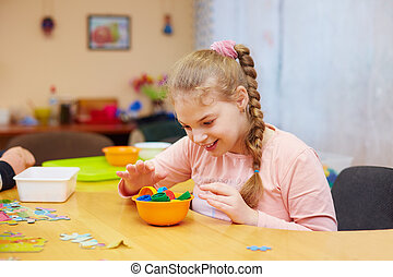 cute happy girl with disability develops the fine motor...