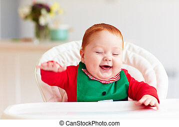 cute happy infant baby boy in elf costume sitting in...