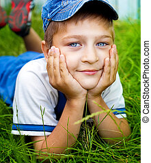 Cute happy kid laying on grass outdoor - Cute happy kid...