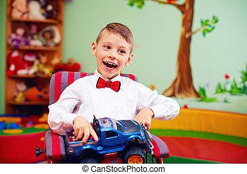 cute happy kid on wheelchair with present in kindergarten...