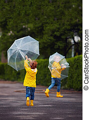 cute happy kids, brothers having fun, playing and running with umbrellas in the park after spring rain
