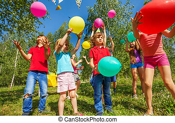 Cute happy kids playing with colorful balloons