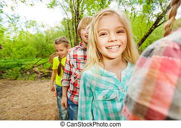 Cute happy kids walking together in the forest