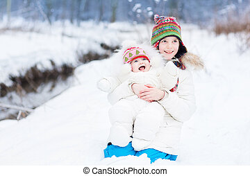 Cute happy laughing brother and baby sister playing in snow on a