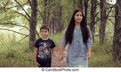 Cute happy little brother and sister are walking holding hands smiling in sunny summer weather
