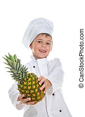 Cute happy little chef holding pineapple on white background.