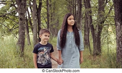 Cute happy little girl and boy are walking holding hands smiling