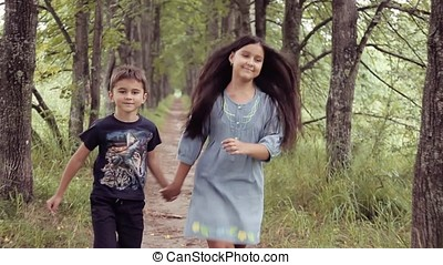 Cute happy little girl and boy running holding hands smiling. Brother and sister are together forever
