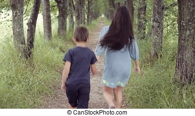 Cute happy little girl and boy running through the forest holding hands smiling. Brother with sisters for a walk
