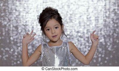 cute happy little girl child in a silver dress dancing on...