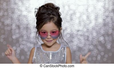 cute happy little girl child in a silver dress dancing on background of silver bokeh.