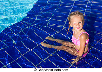 Cute happy little girl in the swimming pool looks at camera