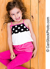 Cute happy little girl lying on the floor