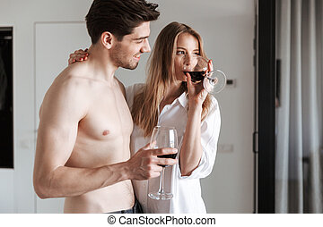 Cute happy loving couple in home indoors drinking wine.