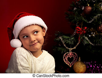 Cute happy smiling girl in fur santa claus hat near the Christmas holiday tree thinking about the gift with grimacing face and looking up. Closeup bright portrait