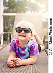 Cute Happy Toddler Girl Smiling as She Lays Outside by the Pool, Wearing Sunglasses