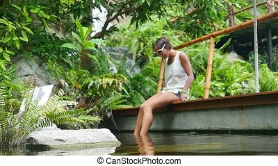 Cute happy young woman wearing sunglasses has fish spa in natural pond by the watefall. in slow motion.
