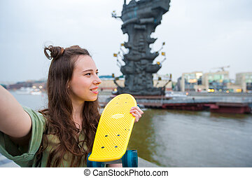 Cute hipster girl makihg selfie with skateboard outdoors in sunset light. Active sporty woman having fun in skate park.