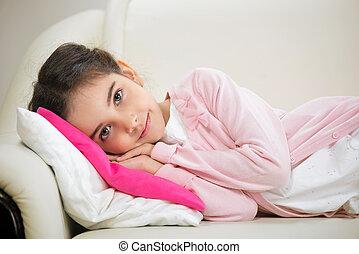 Cute hispanic girl lying in bed