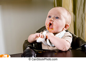 Cute hungry baby eating solid food