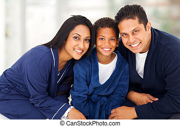 cute indian family sitting on bed