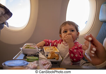 cute infant airplane passenger eats special baby onboard meal diring flight