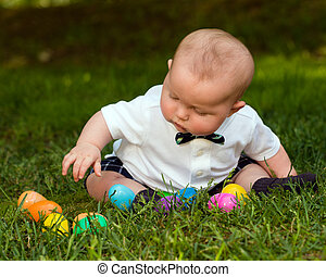 Cute infant baby boy playing with Easter eggs