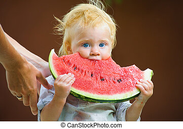 Cute infant baby with a delicious melon